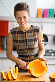 Portrait of smiling young housewife cutting pumpkin in kitchen