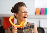 Smiling young housewife using pumpkin slice as phone handset