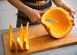 Closeup on young housewife cutting pumpkin