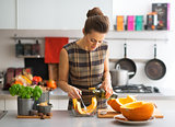 Young housewife cooking pumpkin in kitchen