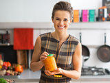 Portrait of happy young housewife showing jar of pickled pumpkin
