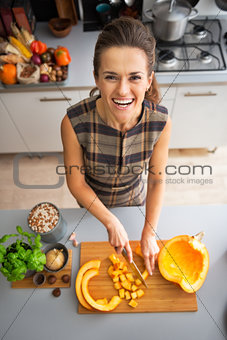 Portrait of happy young housewife cutting pumpkin in kitchen
