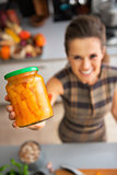Closeup on happy young housewife showing jar of pickled pumpkin