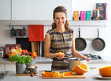 Portrait of happy young housewife cooking pumpkin