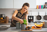 Happy young housewife using fresh basil while cooking in kitchen