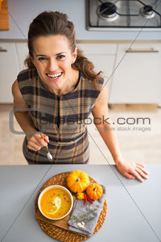 Portrait of happy young housewife eating pumpkin soup