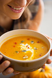 Closeup on young woman enjoying pumpkin soup