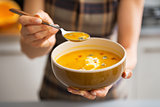 Young woman showing pumpkin soup