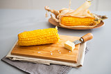 Closeup on boiled corn and butter on cutting board