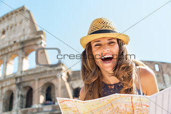 Portrait of happy young woman with map in front of colosseum in