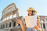 Happy young woman with map in front of colosseum in rome, italy