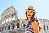 Smiling young woman pointing on colosseum in rome, italy