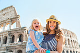 Portrait of happy mother and baby girl in front of colosseum in