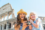 Happy mother and baby girl with photo camera near colosseum in r
