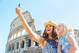 Happy mother and baby girl making selfie in front of colosseum i
