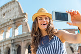 Smiling young woman making selfie in front of colosseum in rome,