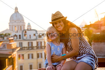 Portrait of happy mother and baby girl sitting on street overloo