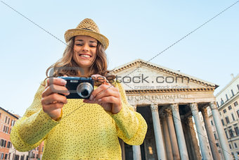 Portrait of happy young woman checking photos in camera in front