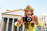 Smiling young woman taking photo in front of pantheon in rome, i