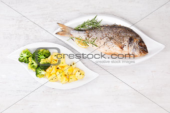 Grilled sea bream with potatoes on plate.