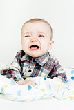 Adorable baby screaming in a plaid shirt