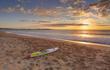 Beach sunrise and paddleboard on shoreline