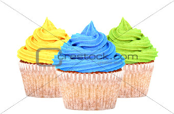 Three cupcakes with yellow, blue and green icing