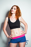 Studio fashion shot: beautiful redhead woman wearing shorts and shirt