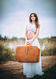 Beautiful young woman with suitcase in hands stands on field road