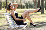 Funny female model of fashion with high heels sitting on a bench