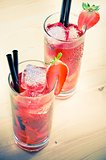 glasses of strawberry cocktail with ice on old wood table, old style