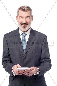 Aged entrepreneur holding tablet pc