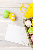 Easter background with colorful eggs, yellow tulips and greeting