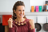 Portrait of happy young housewife using mushrooms on string as n