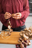 Closeup on young housewife stringing mushrooms on string