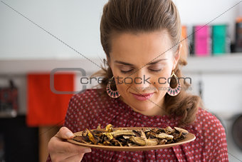 Portrait of young housewife smelling dried mushrooms