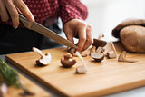 Closeup on young housewife cutting mushrooms in kitchen