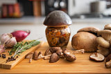 Closeup on jar of pickled mushroom on cutting board
