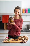 Happy young housewife showing jar of pickled mushrooms