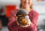 Closeup on happy young housewife showing jar of pickled mushroom