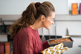 Young housewife smelling baking dish with bread