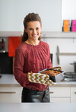 Portrait of happy young housewife with baking dish with bread