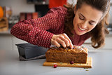 Closeup on happy young housewife decorating freshly baked pumpki