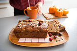 Closeup on freshly baked pumpkin bread with seeds and young hous