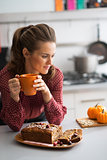 Young housewife drinking tea with freshly baked pumpkin bread wi