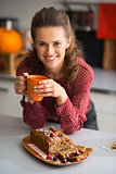 Happy young housewife drinking tea with freshly baked pumpkin br