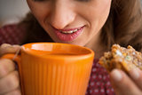 Closeup on young housewife drinking tea with freshly baked pumpk