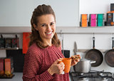 Portrait of happy young housewife drinking tea with freshly bake