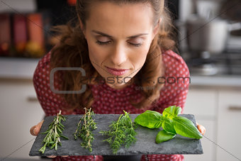 Portrait of young housewife enjoying fresh spices herbs
