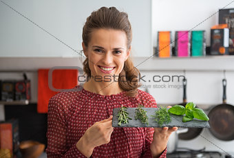 Portrait of happy young housewife showing fresh spices herbs on